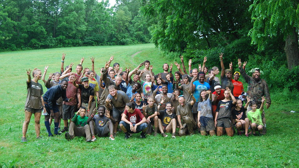 muddy group photo after obstacle course
